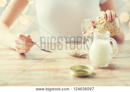 food, healthy eating, people and diet concept - close up of woman eating muesli with milk for breakfast over holidays lights background