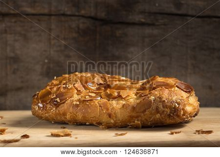 Strudel with almonds and vanilla ice cream over rustic wooden background