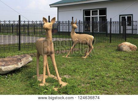 Novotyryshkino, Russia - July 31, 2013: Sculptures of deer on the lawn. Tourist Complex Siberian Podvorye.