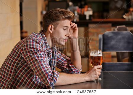 Young man sitting alone in a bar
