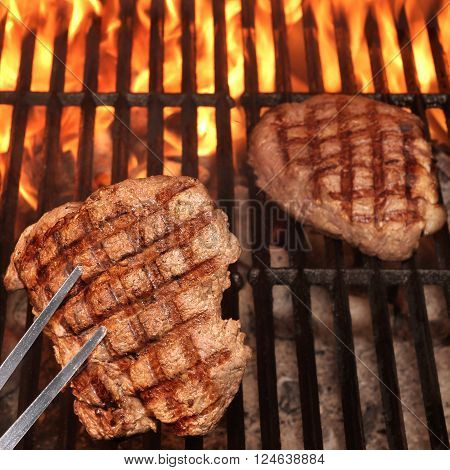 Two Beef Steaks On The Hot BBQ Charcoal Grill With Flame Of Fire Close Up Top View. Outdoor Scene. Concept for Summer Party Or Picnic Or Cookout.