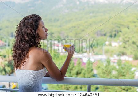 Woman is drinking orange juice on the hotel balcony.  Green nature on the background.