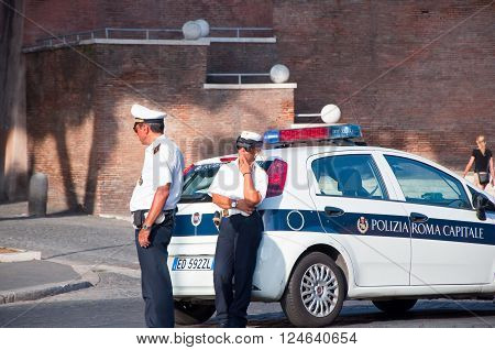 ROME-AUGUST 8: Italian Police patrol on Via dei Fori Imperiali on August 82013 in Rome. The Via dei Fori Imperiali is a road in that runs in a straight line from the Piazza Venezia to the Colosseum.