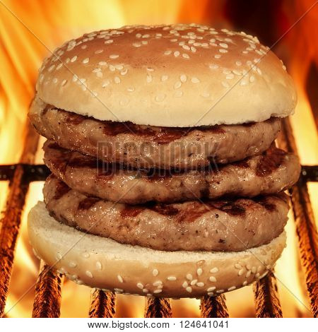 Homemade Big Hamburger On The Hot Flaming BBQ Grill Close Up Front View Cookout Food For Outdoor Party Or Picnic