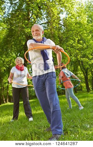 Senior group with hoops in a fitness class exercising in nature in a garden