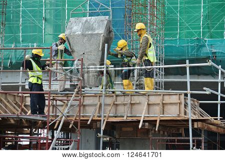 SELANGOR, MALAYSIA - DECEMBER 12, 2015: A group of construction workers pouring wet concrete using concrete bucket into the timber form work at the construction site
