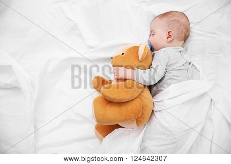 Loving baby with teddy bear sleeping on soft bed, close up