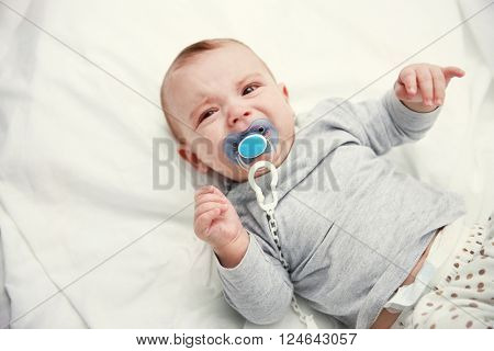 Crying baby with dummy lying on soft bed, close up