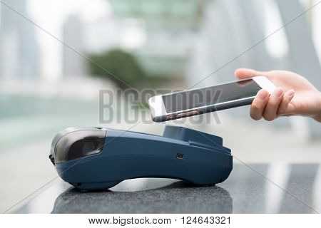 Woman pay by mobile phone with NFC technology