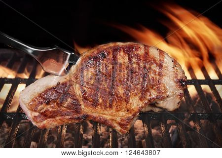Pork Steak On Hot Flaming Barbecue Grill With Fork