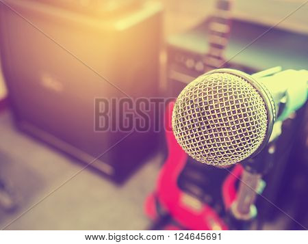Microphone in a recording studio or concert hall with amplifier in out of focus background. Vintage style and filtered process.