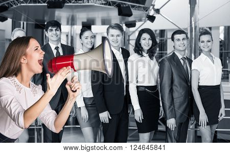 Business woman stands with megaphone on the blurred people background