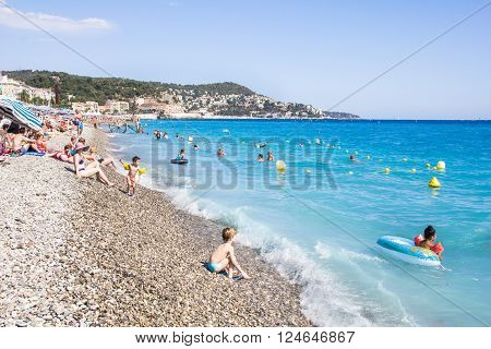 NICE, FRANCE - AUGUST 23, 2015: Tourists enjoy the good weather at the beach in Nice, France. The beach and the waterfront avenue Promenade des Anglais are full almost all the year.