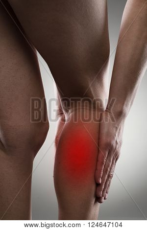 Young female touching her leg calf in pain over grey background