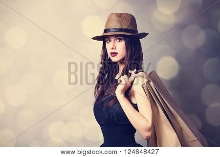 portrait of the beautiful young woman with shopping bags on the grey background
