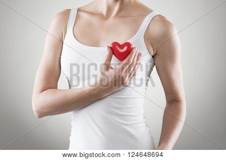 Close-up of female' body holding red heart at breast. Heartburn or infarct concept.
