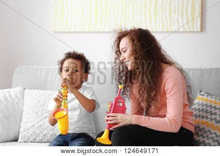 Little boy and a young girl playing  with musical toys on the couch