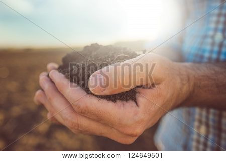 Farmer holding pile of arable soil male agronomist examining quality of fertile agricultural land close up with selective focus
