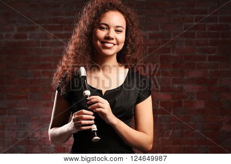 Beautiful young woman holding a recorder over brick wall background