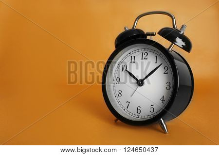 Alarm clock on brown background.