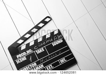Movie clapperboard on wooden background