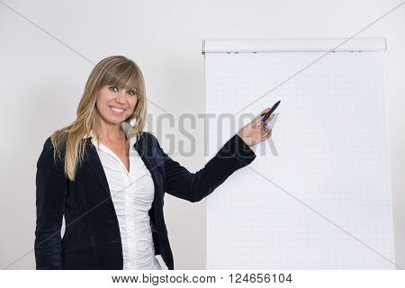A businesswoman is pointing at a flip chart with a pen. The woman is looking to the camera.
