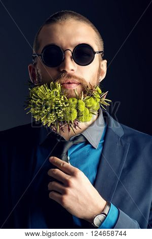 Handsome man in sunglasses and with a beard of green flowers smiling at camera. Men's beauty. Barbershop.