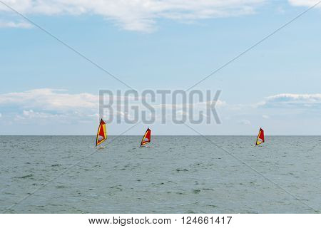 Windsurfing board in sea with skyline and clouds