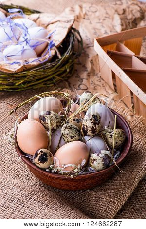 fresh hen and quail's eggs in a brown bowl