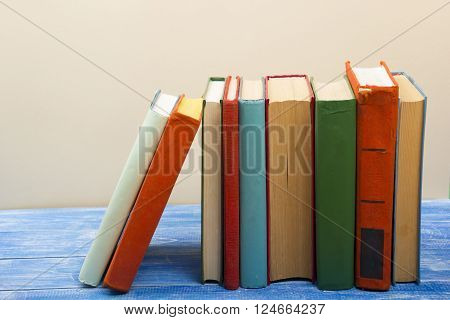 Stack of hardback books on wooden table. Back to school. Copy space for text.