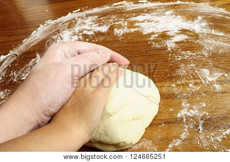 Child and adult hands kneading bread dough