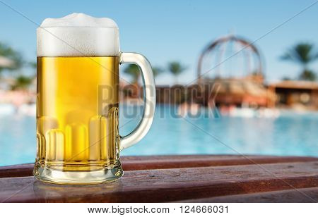 Mug of light beer near the swimming pool.