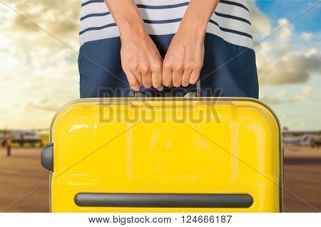 Hand holds suitcase.