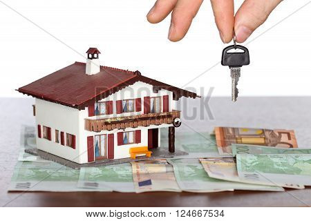 symbolic key in hand with house model in background