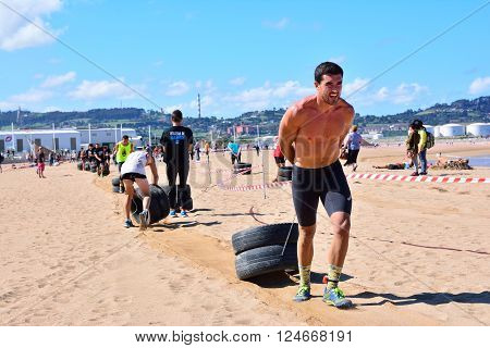 GIJON SPAIN - SEPTEMBER 19: Storm Race an extreme obstacle course in September 19 2015 in Gijon Spain. Participants in extreme obstacle course dragging wheels