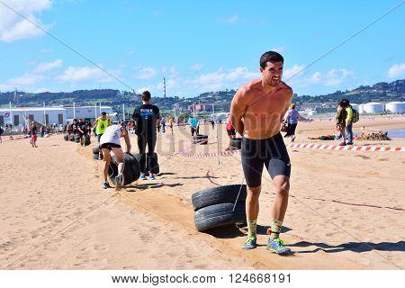 GIJON SPAIN - SEPTEMBER 19: Storm Race an extreme obstacle course in September 19 2015 in Gijon Spain. Participants in extreme obstacle course dragging wheels