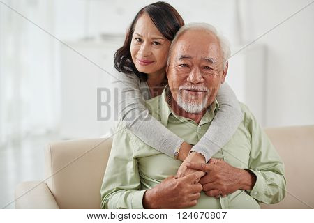 Happy smiling aged woman hugging her husband from behind