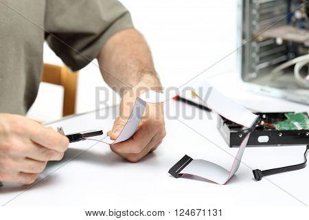 computer worker is repairing a machine on desk