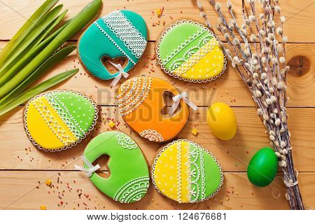 Easter homemade gingerbread cookie and yellow end green eggs over wooden table. Colorful image top view