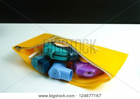 Asthma relief concept salbutamol inhaler another medication and yellow medical plastic bag copy space isolated on white