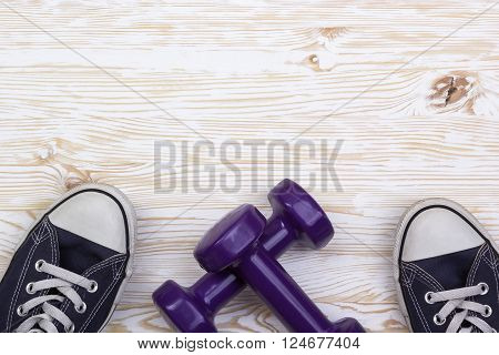 Fitness and sport equipment :sneakers and dumbbells with wooden background on top view