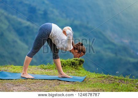 Woman doing Ashtanga Vinyasa yoga asana Parsvottanasana intense side stretch pose  outdoors in mountains Himalayas. Himachal Pradesh, India