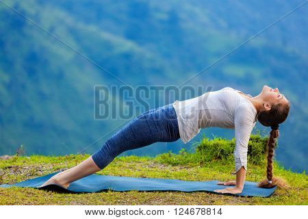 Woman doing Hatha yoga asana Purvottanasana plank pose  outdoors in mountains