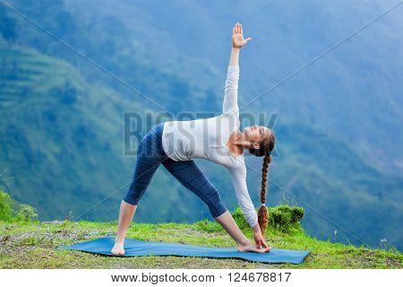 Woman doing Ashtanga Vinyasa yoga asana Utthita trikonasana - extended triangle pose outdoors