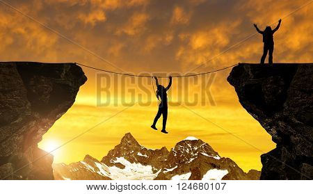 Silhouette girl climbs on a rope over an abyss at sunset.