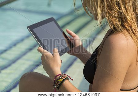 Young attractive blond woman sitting next to a swimming pool and surfing the web on a tablet computer