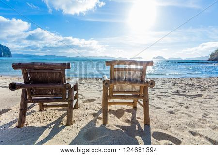 Two deckchairs on the tropical beach with bright sun
