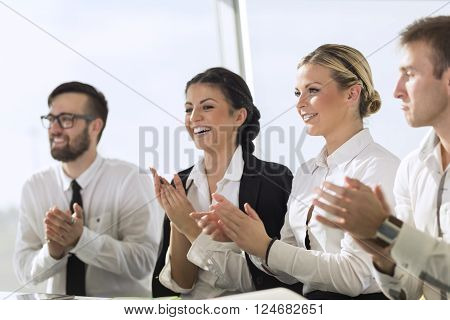 Busines team applauding a colleague on a successful presentation