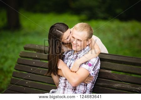 Woman in love kissing happy man in park on cheek