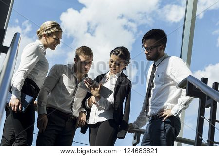 Business team standing next to window on a staircase in an office building preparing for a meeting